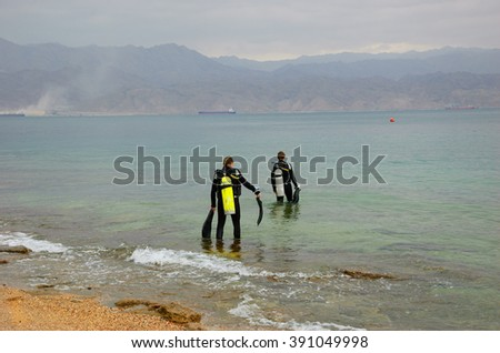 Two friends going to dive (Eialt, Israel). Coral Beach Nature Reserve in Eilat, one of the most beautiful coral reef in the world, is famous tourist and diver attraction. - stock photo