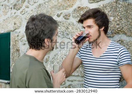 two friends having a drink and talking outdoors - stock photo