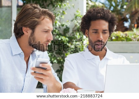 Two friends having coffee together with laptop outside at the coffee shop - stock photo