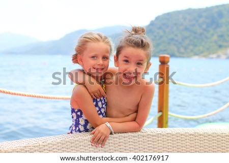 two friends having fun, they rest on a sunny day at sea
