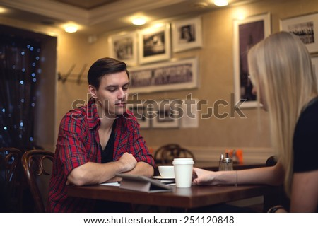 Two friends hipster man young woman are sitting in front of each other in the cafe and chat with a cup of coffee. - stock photo