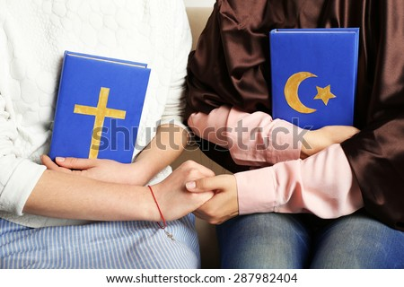 Two friends holding books with religions symbols - stock photo