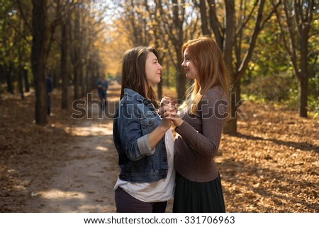 Two friends hugging in the park