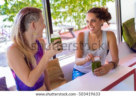 Two friends in a yoga studio drinking a green juice
