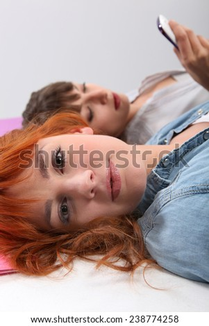 Two friends laying on their bed. - stock photo