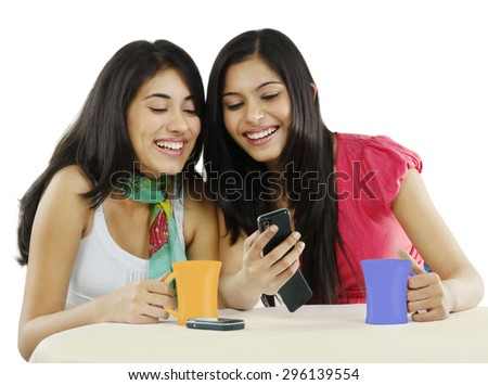 Two friends looking at a mobile phone and smiling - stock photo