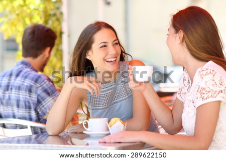 Two friends or sisters talking taking a conversation in a coffee shop terrace looking each other - stock photo