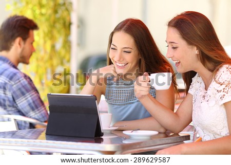 Two friends or sisters watching videos in a tablet in a coffee shop terrace