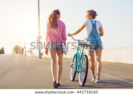 Two friends out for a bike ride at the seaside. Stylish casual outfit - stock photo
