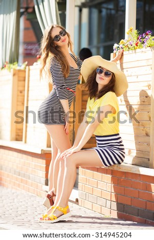 two friends outdoors. two girls having fun. Smiling women outdoor. two beautiful young women having fun in the city. Two women friends laughing with a perfect white teeth - stock photo