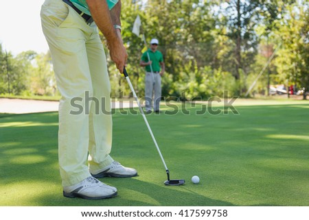 Two friends playing golf - stock photo