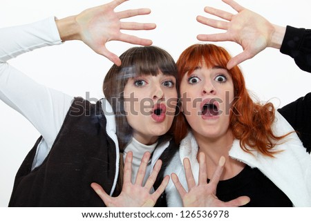 Two friends pressing their face on a pane. - stock photo
