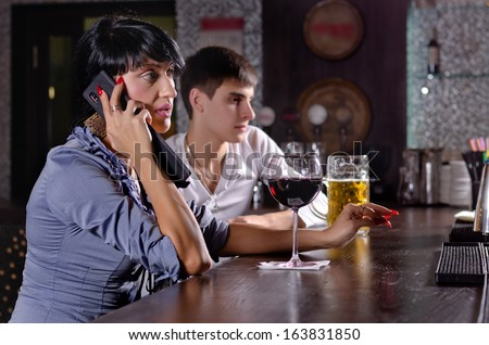 Two friends relaxing together drinking at the bar with a woman talking on a mobile phone with a serious expression and a large glass of red wine in front of her - stock photo