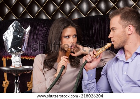 two friends resting in Arabic cafe. man and woman smoking hookah and looking - stock photo
