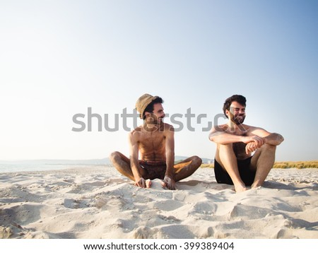 Two friends seating on the beach together - stock photo