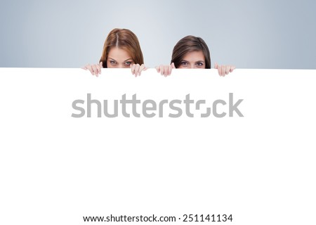 Two friends secretly hiding behind a blank poster against grey vignette - stock photo