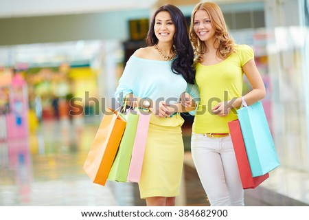 Two friends shopping together in shopping mall - stock photo