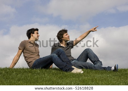 Two friends sit on the grass looking up