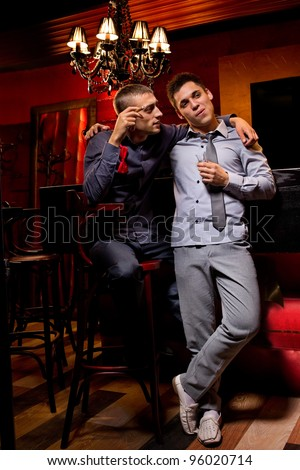 Two friends sitting in a pub drinking a short and smoking a cigar - stock photo