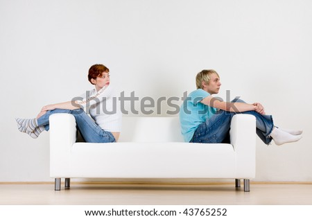 Two friends sitting on opposite ends of a white couch.