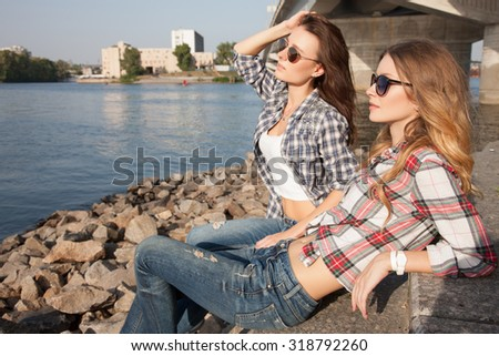 Two friends sitting on the promenade near the pier and looking into the distance.Beautiful model goes through the city on foot. Looking on the outskirts of the city.