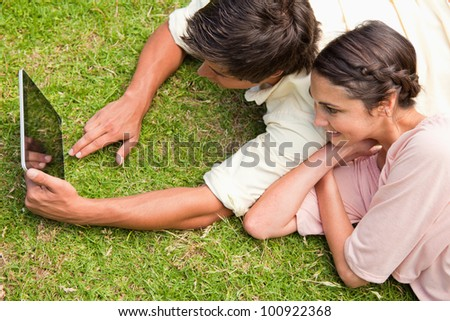Two friends smiling as they use a tablet together while lying down on the grass - stock photo