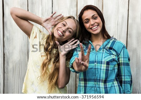 Two friends smiling at camera making gesture - stock photo