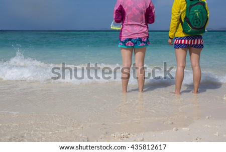 Two friends stand at the beautiful ocean. White sandy beach, crystal clear water