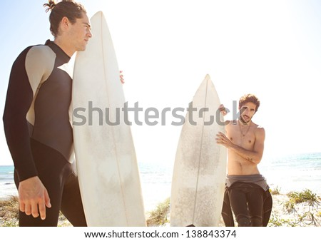 Two friends standing together on a white sand beach dunes, holding their surfing boards and getting ready for surfing while wearing neoprene rubber suits during a sunny day. - stock photo