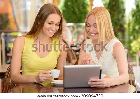 Two friends talking and drinking coffee, sitting in a cafe outdoors
