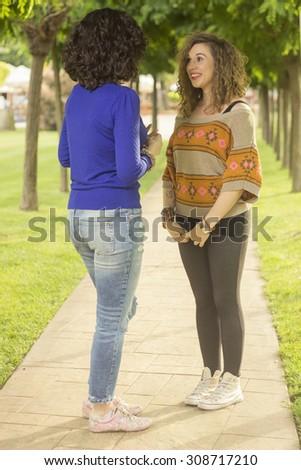Two friends talking to each other, in park on a pavement.