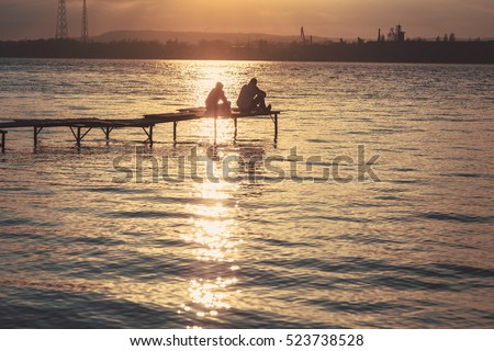 Two friends-teenagers sitting on a wooden pier against dramatic sunset over the river.