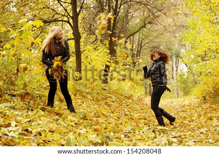 two friends throw each other autumn leaves - stock photo