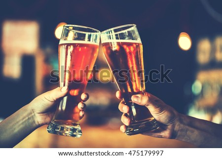 Two friends toasting with glasses of light beer at the pub. Beautiful background of the Oktoberfest. fine grain. Soft focus. Shallow DOF. Blue toned