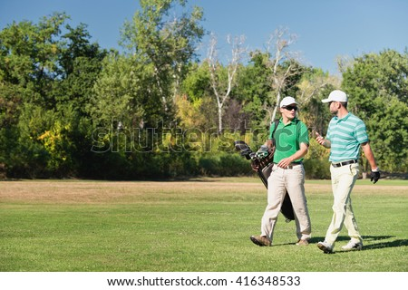 Two friends walking down the golf course