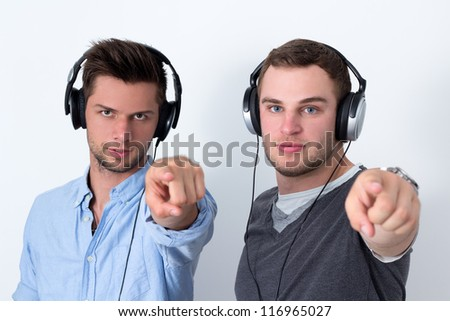 Two friends with headphone listening to music in front of a white background and pointing at camera