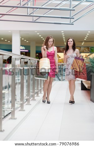 Two friends with purchases in the big shopping center