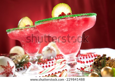 Two frozen pomegranate margaritas cocktails on Christmas decorated holiday table with Christmas ornaments. Holiday cocktails series.  - stock photo