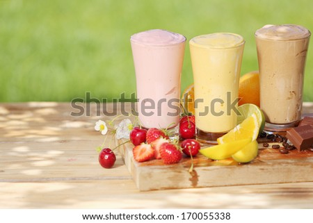 Two fruit smoothie drinks and one chocolate smoothie in tall glasses on a wooden board outdoors. - stock photo