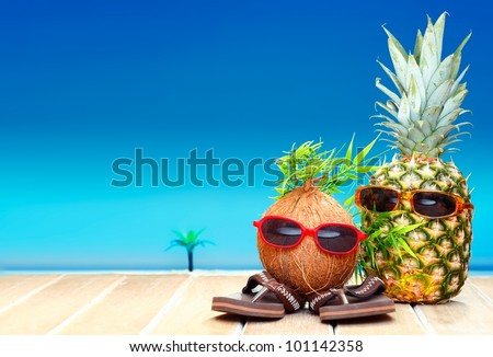 Two fruity friends, a coconut and pineapple, with fun foliage haistyles and trendy sunglasses in tropical paradise - stock photo