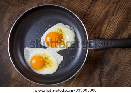 two frying eggs with spices on black pan with wooden background - stock photo