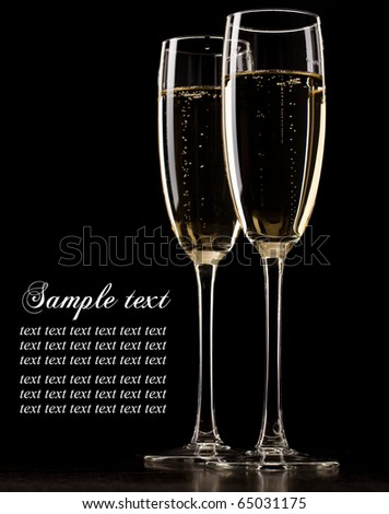 Two full glasses of champagne over dark background - stock photo