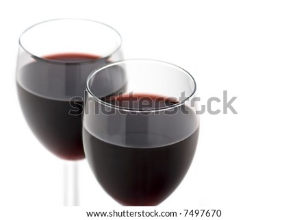 Two Full Wine Glasses with Focus on Front Rim of Closest Glass with Loads of Copy Space - stock photo