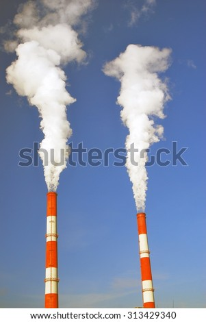 Two fuming tubes. Blue sky background. - stock photo