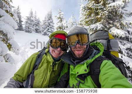 Two funnny hikers posing at camera in winter mountains - stock photo