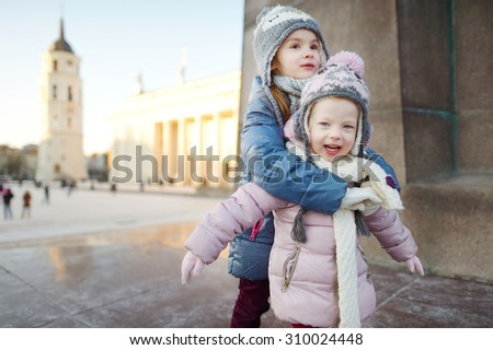 Two funny adorable little sisters having fun together at winter Vilnius - stock photo