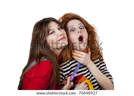 Two funny angry girls. One of them strangle to other. Studio shot.