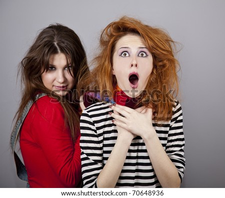 Two funny angry girls. One of them strangle to other. Studio shot. - stock photo