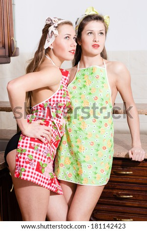 two funny beautiful young woman attractive pinup girl friends standing in aprons & looking up