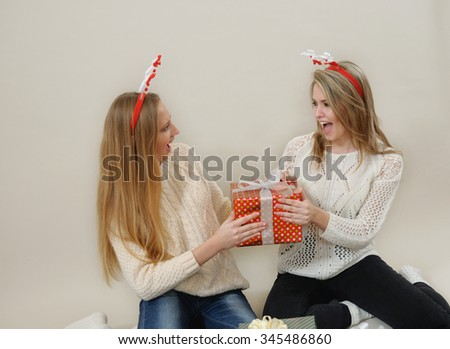 Two funny girls fighting over a gift boxes. Christmas and New Year concept. Studio shot on grey background. - stock photo